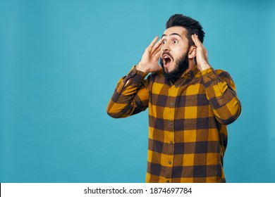 surprised man on blue background touching head with hands and yellow shirt emotions model