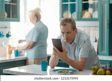 Surprised man reading bad news on a mobile phone while having morning tea. Family breakfast, retirement.
