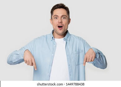 Surprised man showing index fingers down isolated on gray background. Astonished male editable advertisement banner, copy space, sale, bargain concept. Model posing at studio during photoshoot