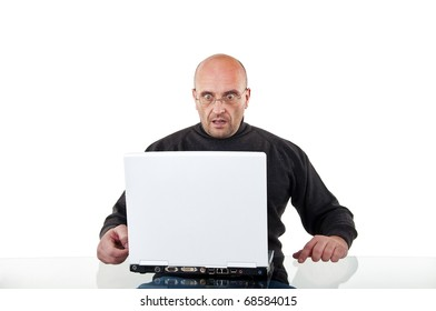 Surprised man sits at the desk with a laptop, isolated on white