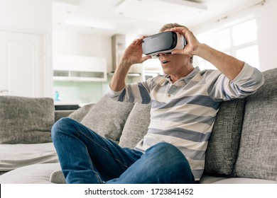 surprised man touching virtual reality headset while sitting on sofa at home