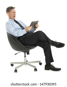 Surprised mature businessman looking at tablet computer while sitting on office chair against white background