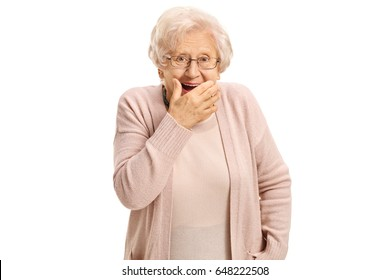 Surprised mature woman holding her hand against her mouth and looking at the camera isolated on white background