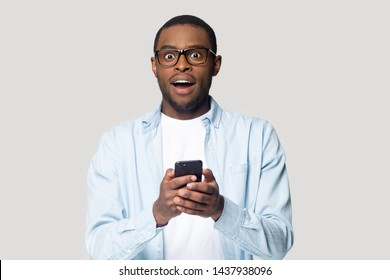 Surprised millennial african american man isolated on grey studio background hold smartphone get good unexpected message, excited black male in glasses look at camera shocked by online sale