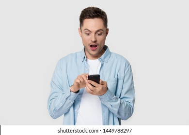 Surprised millennial man holding cellphone looking at telephone screen. Astonished guy scrolling new smartphone in hands isolated on grey background posing at studio photoshoot. Advertising technology