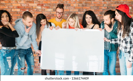 Surprised millennials holding blank whiteboard mockup. Young emotional people looking impressed with copy space for supposed content.