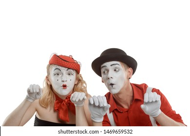 Surprised mime man and woman looking over the invisible wall. Pantomime art and funny show concept.