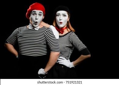 Surprised mimes, isolated on black. Couple of male and female actors expressing different emotions during a pantomime show.