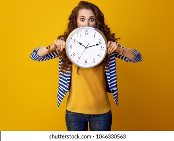 surprised modern woman with long wavy brunette hair isolated on yellow background hiding behind clock