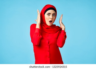 surprised muslim woman in red burqa on blue background