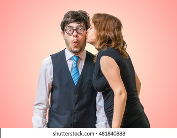 Surprised nerd is being kissed by pretty woman.
