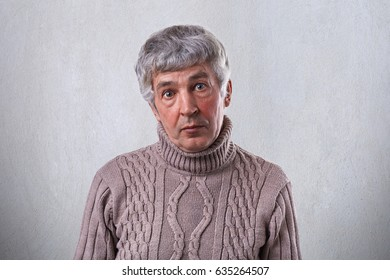 A surprised old man with dark eyes having wrinkles on his face and gray hair wearing brown sweater looking directly into camera with wide opened eyes.