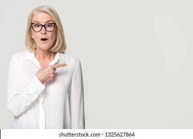 Surprised old mature businesswoman pointing finger at copy space looking at camera, amazed senior middle aged woman in glasses advertising product service isolated on white grey studio background