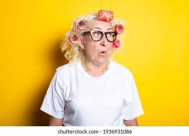 Surprised old woman with curlers in glasses, in a white T-shirt on a yellow background.