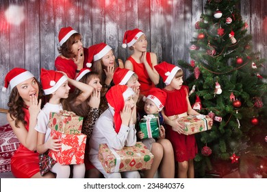 surprised people in santa cluas hats holding presents and looking at Christmas tree