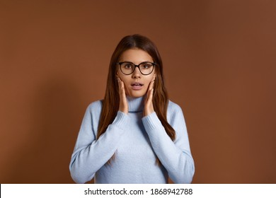 Surprised pretty caucasian female keeps palms near face, expresses amazement, has mouth open, can not believe in shocking news, wears glasses and light blue sweater, isolated on brown background