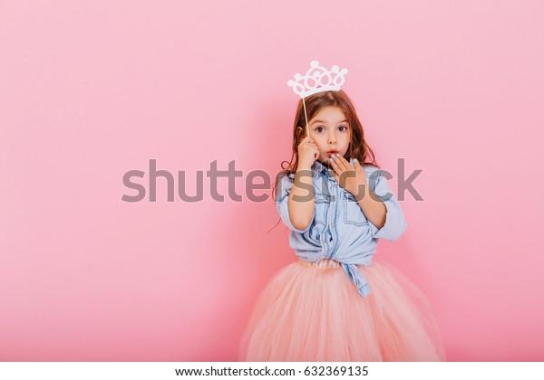 ピンクの背景に頭に王冠を持つ、驚いた小さな少女がタルスカートに姿を現した。カーニバルのかわいいお姫様。テキストの配置
