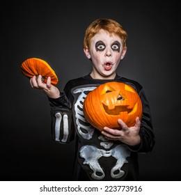 Surprised red haired boy in Halloween costume holding a orange pumpkin. Skeleton. Studio portrait over black background