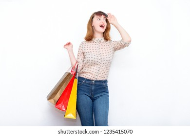 Surprised red-haired woman after shopping with bags in her hands on a light background in casual clothes. The modern concept of shopping, sales, discounts, fashion and lifestyle.