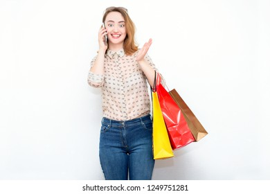 Surprised red-haired woman in stylish casual clothes with bags after shopping and talking on the phone. Modern concept of fashion, shopping, discounts, sales.