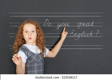 Surprised redhead girl asks a question -  Do you speak English, stand near blackboard in the classroom. Education concept.