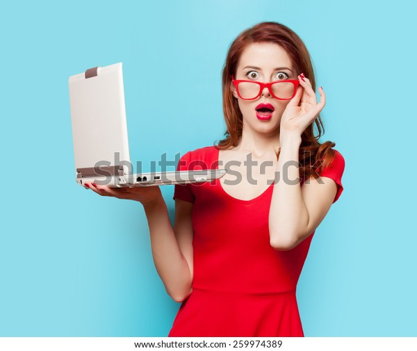 Sorprendida chica pelirroja con portátil de fondo azul