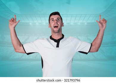 Surprised rugby player pointing up against blue vignette background