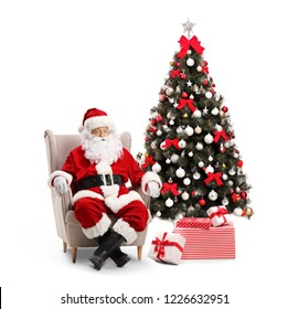 Surprised Santa Claus sitting in an armchair with a decorated Christmas tree next to him isolated on white background