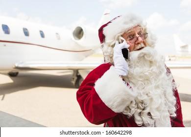 Surprised Santa Claus using mobile phone against private jet at airport terminal