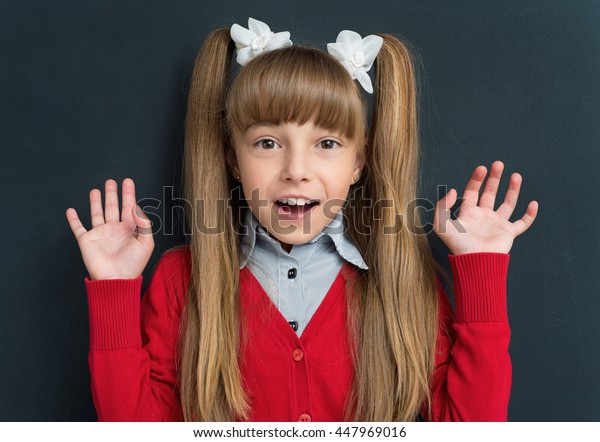 Surprised schoolgirl at the chalkboard background in class. Back to school concept.