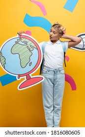 surprised schoolgirl touching head while holding globe maquette near paper pencil and decorative elements on yellow