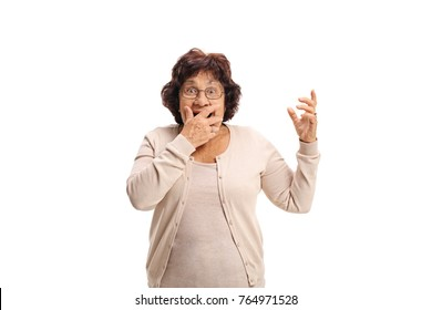 Surprised senior lady covering her mouth with her hand and looking at the camera isolated on white background