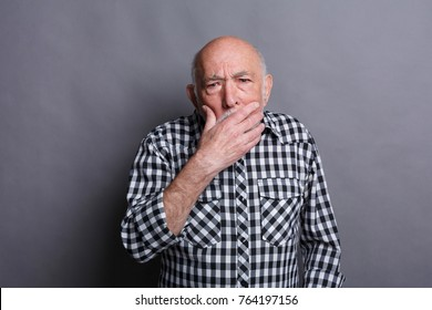 Surprised senior man covering mouth with hand. Keep silence. Gossip, shock concept, copy space