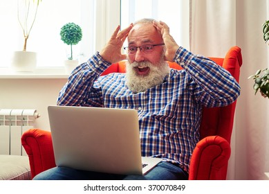 surprised senior man with laptop sitting on the chair at home