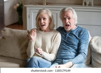 Surprised senior middle aged couple viewers feeling amazed watching new reality show on television channel, astonished shocked old mature family looking excited by unbelievable breaking news on tv