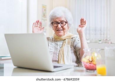 Surprised senior woman communicating via instant messaging apps on laptop.