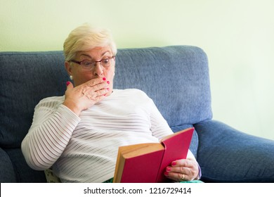 Surprised senior woman with eyeglasses reading red book sitting on sofa. Elder blonde lady holding novel and covering mouth with hand in living room couch. Scary, mystery, suspense tale concepts