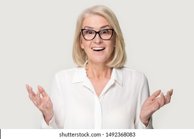 Surprised senior woman in glasses stand isolated on grey studio background feel amazed stunned with good sale offer, shocked mature lady wear spectacles look at camera hold blank copy space place
