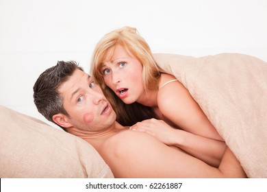 Surprised sex couple lying in bed with lipstick kiss