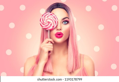 Surprised sexy girl eating lollipop. Beauty Glamour Model woman with trendy pink hair style and beautiful makeup holding pink sweet colorful lollipop candy, on pink polka dots background. Sweets