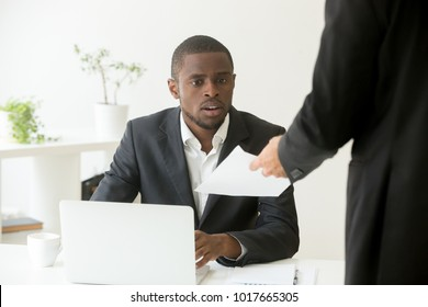 Surprised shocked african businessman getting unexpected dismissal notice from caucasian boss colleague, black employee astonished by notification about debt or letter with bad news, getting fired