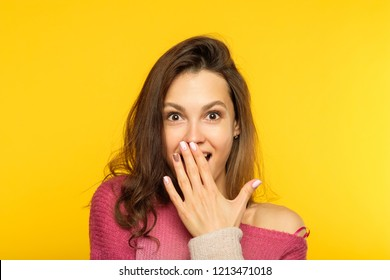 surprised shocked astonished amazed girl covering mouth with hand. unbelievable news. young beautiful woman on yellow background. emotional reaction concept.