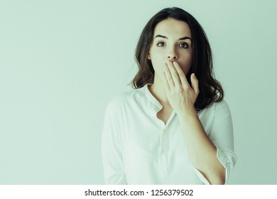 Surprised and shocked girl learning news or gossip. Young Caucasian woman in white blouse covering mouth with hand and keeping silence or secret. Good or bad news and secrecy concept