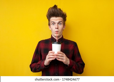 surprised shocked guy drinks energy coffee on a yellow isolated background, a man with a funny hairstyle holds an invigorating drink
