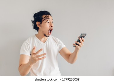 Surprised and shocked long hair Asian man in white t-shirt is using smartphone.