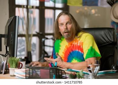 Surprised or shocked man in tie dye shirt at his desk