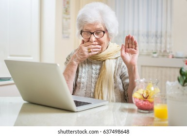 Surprised or shocked senior woman using laptop at home.