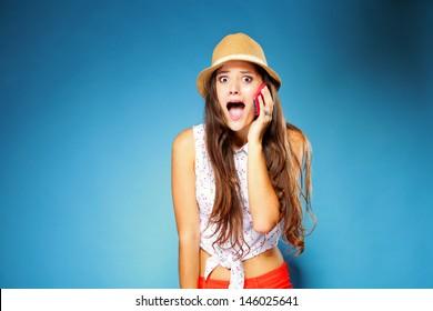 Surprised shocked summer girl talking on mobile phone, blue background