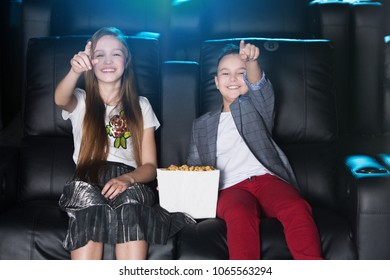 Surprised smiling little girl and boy sitting at the cinema, watching a film and eating popcorn. movie theater.