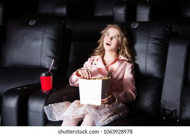 Surprised smiling little girl sitting at the cinema, watching a film and eating popcorn. movie theater.